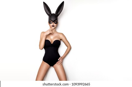 Sexy woman in a black bunny mask on a white background.