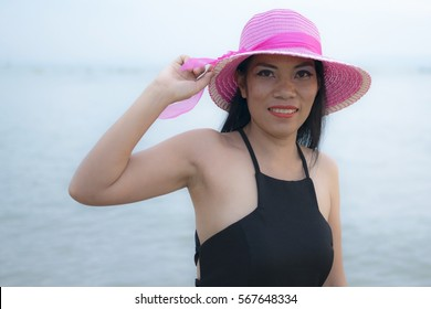 Sexy woman with black dress posing on the beach