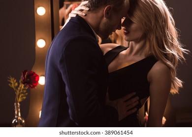 Sexy woman in black dress seducing a man