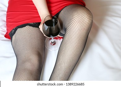 Sexy woman in black fishnet stockings with a glass of red wine in the bed. Drunk hot girl, concept of celebration, relax, female alcoholism, sex dating