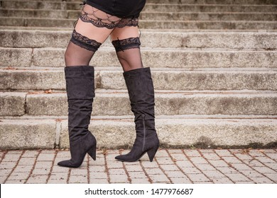 Sexy woman in black lacy stockings and suspenders wearing knee high boots posing in front of outdoor steps in town in a low angle view of her legs in a conceptual image