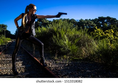 Sexy woman in black leather clothes with gun. Gangsta girl with weapon on the abandoned railway.