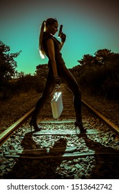 Sexy woman in black leather clothes holding a suitcase and gun. Gangsta girl with weapon on the abandoned railway at night.
