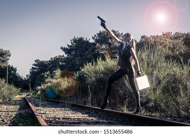 Sexy woman in black leather clothes with gun and suitcase. Gangsta girl with weapon on the abandoned railway at night.