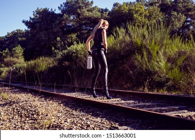 Sexy woman in black leather clothes with suitcase. Gangsta girl with weapon on the abandoned railway.