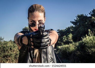 Sexy woman in black leather clothes and sunglasses with gun. Gangsta girl closeup portrait with weapon.