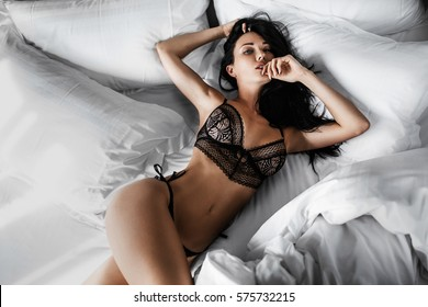 sexy woman in black lingerie lying in bed