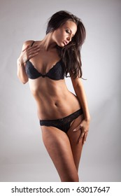 Sexy woman. Black lingerie  on grey background
