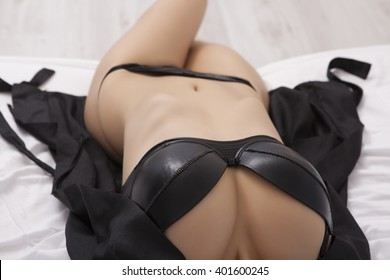 Sexy woman in black lingerie resting on bed . Erotic pose