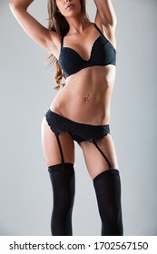 Sexy woman in black lingerie and black stockings in studio