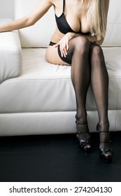 Sexy Woman in black stockings on sofa, with high heels resting on sofa . Erotic pose