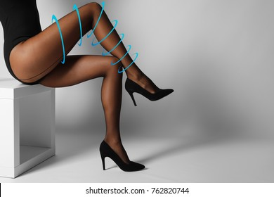 Sexy woman in black tights with shaping effect on light background