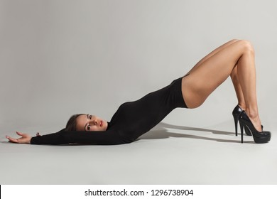 sexy woman in black turtleneck and black shoes lying in white background