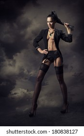 Sexy Woman in black underwear lingerie and stockings over dark sky background