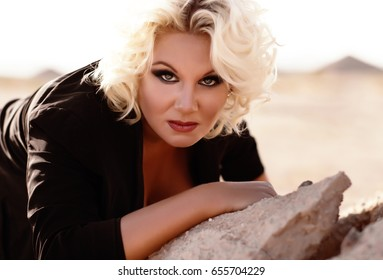 Sexy woman with blond curly hair and deep eyes with long eyelashes, red lips, attractive horny look, fashion beauty, beautiful bright make up, plus size model, erotic big fat girl in black open dress