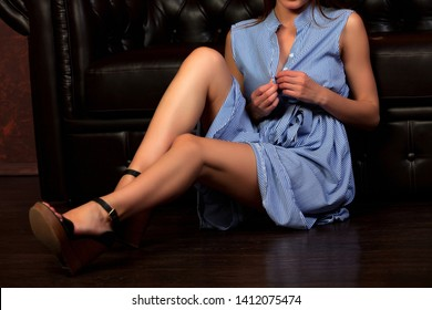 Sexy woman in blue and white dress sitting on the floor and undressing.