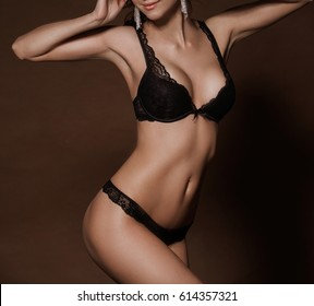 Sexy woman body in black lingerie on brown background