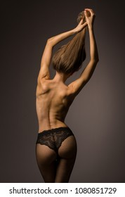 Sexy woman body half-naked, from behind. Beautiful artistic studio picture.