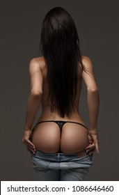 Sexy woman body in jeans, stripper. Great ass. Sexy female wearing a of pants. Sexual girl takes off her jeans. Seductive woman standing with her back to the camera and shows a beautiful ass, butt.
