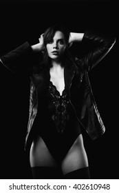 Sexy woman in body lingerie and leather jacket in black and white image looking sensual at the camera