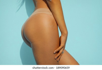 Sexy woman buttock on turquoise background. Tanned skin.  Horizontal shot, soft colors