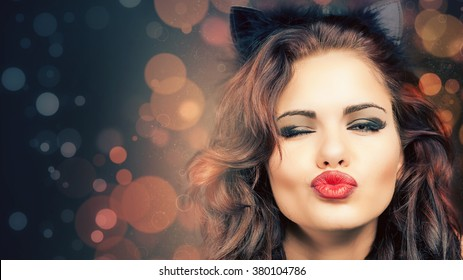 Sexy woman with carnival cat ears at Venetian party. Halloween. Blow kiss. Fashion. Venetian carnival. Sex shop. Hot babe. Party. Night girl. Blur