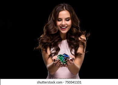 Sexy woman in a chic gently pink dress holding colored poker chips. Woman winning