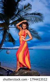 Sexy woman in colorful dress posing on the beach rocks at sunset