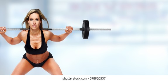 Sexy woman doing squat with barbell.