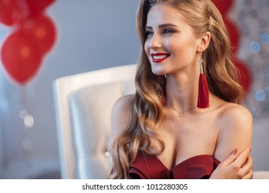 sexy woman in dress sitting in armchair. fashion and beauty. young healthy skin. long hair and makeup
