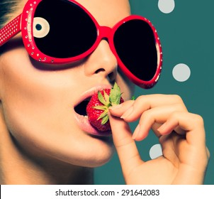 Sexy Woman Eating Strawberry. Sensual Red Lips. Red Manicure and Lipstick. Desire. Sexy red Lips with Strawberry