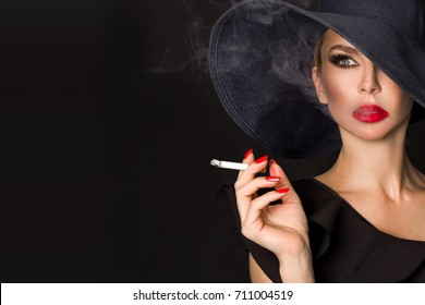 Sexy woman in elegant hat and with red lips blowing smoke, isolated on black. Femme fatale. Elegant lady with cigarette.