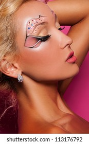 sexy woman with face art on pink background