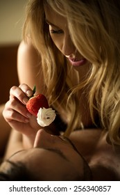 Sexy woman feeding man with strawberry with whipped cream