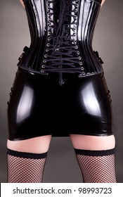 Sexy woman in fetish latex skirt and corset, studio shot