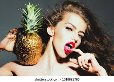 Sexy woman with finger in sensual mouth. Girl with golden pineapple or ananas. Beauty, makeup, look, hair, hairstyle. Fruit, food, vitamin, diet, healthy dieting. Blowjob, handjob, oral sex.