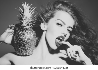 Sexy woman with finger in sensual mouth. Girl with golden pineapple or ananas. Beauty, makeup, look, hair, hairstyle. Fruit, food, vitamin, diet, healthy dieting Blowjob handjob oral sex