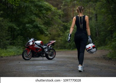 Sexy woman goes to a the superbike motorcycle with helmet in hand