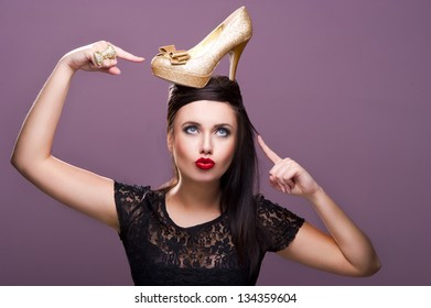 Sexy woman with gold shoe on head