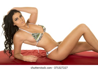 A sexy woman in a green print bikini laying back on a red sheet.