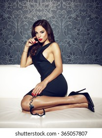 Sexy woman with handcuffs sit on sofa, red lips and nails, bdsm