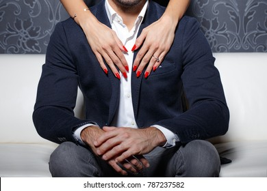 Sexy woman hands with red nails touchning and embracing rich man
