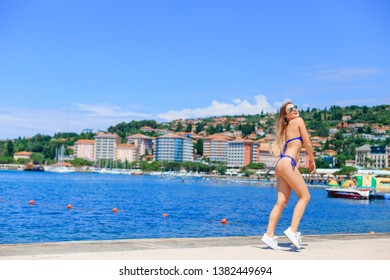 sexy woman has blue swimsuit, sunglasses have fun on a beach. city on the background