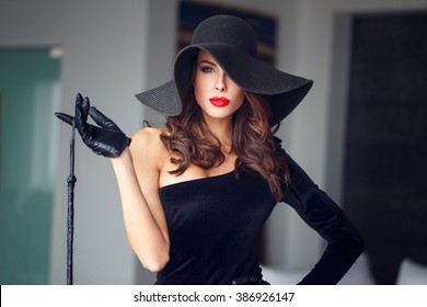 Sexy woman in hat holding whip, bdsm