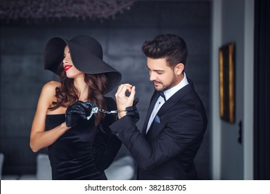 Sexy woman in hat holding young rich lover on handcuffs indoor, teeth smile