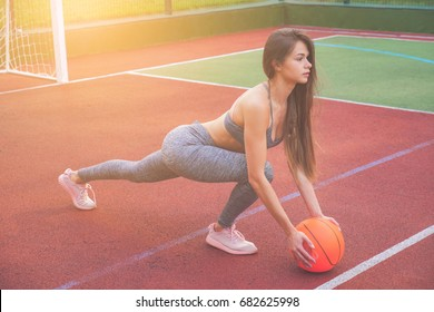Sexy Woman Holding Basketball In Hand On Sports Playground. Beautiful sexy woman player basketball posing outdoors street. Young beautiful female basket ball player.