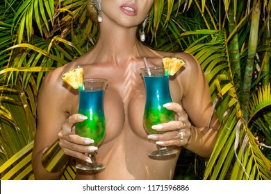 Sexy woman, holding a drink on a Caribbean beach. Colorful drink on the beach among palm trees. The woman covers her breasts with drinks.