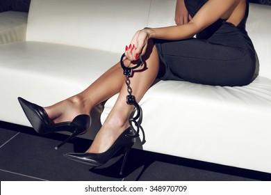 Sexy woman holding handcuffs on sofa, bdsm