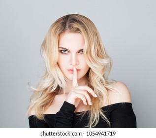 Sexy woman holding her finger to her lips in a gesture for silence
