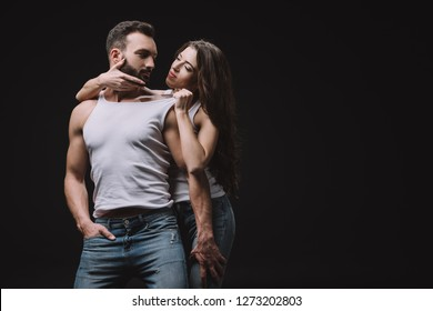 sexy woman hugging and undressing man in white singlet isolated on black
